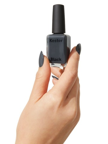 Eine Frauenhand hält einen grauen Nagellack hoch