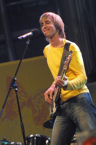 Michael Tschuggnal steht mit Guitarre und Mikro auf der Bühne