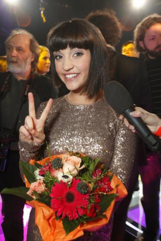 Nadine Beiler macht das Peace-Zeichen in die Kamera, lächelnd mit Blumen