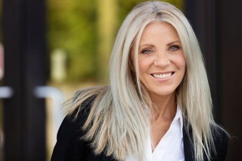 Lächelnde Frau  mit langen graublonden Haaren und Mittelscheitel