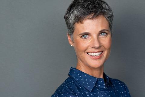 Strahlend lächelnde Frau mit lauen Augen und kurzen grauen Haaren