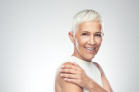 Frau mit sehr kurzen, weiß-silbernem Haarschnitt