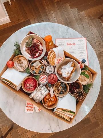 Tisch mit Karton, darin Sandwiches, Pancakes uvm