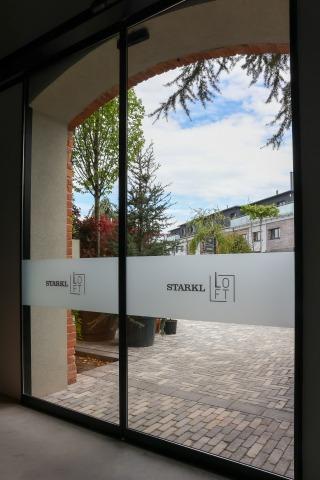 Große automatische Glastür mit Loft Schriftzug