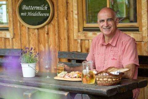 Tourismusmanager Georg Overs sitzt an einem mit einer Jause gedeckten Tisch vor einer Almhütte