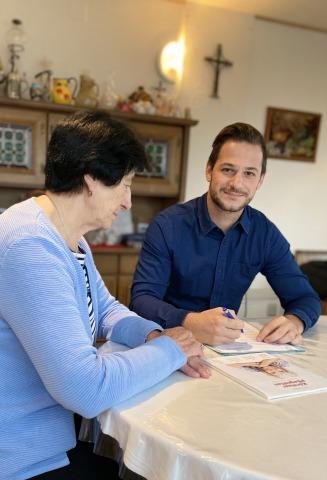 Pflegekoordinator Markus Pernull berät eine ältere Dame in ihrem Wohnzimmer