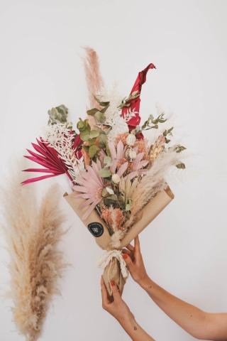 Eine Hand hält einen Strauß mit getrockneten Blumen und Gräsern