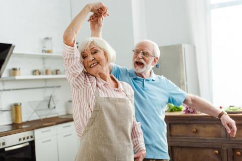 Ein älteres Paar, das beschwingt durch seine Küche tanzt
