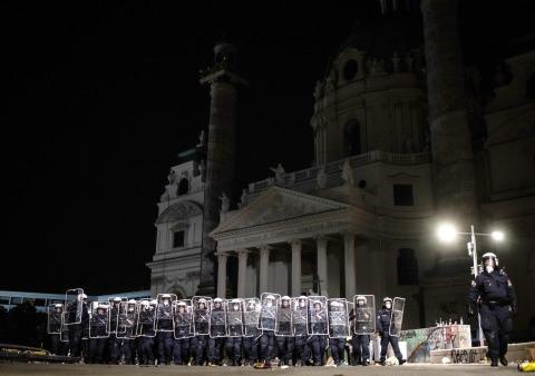 Polizisten schützen sich mit Schildern am nächtlichen Karlsplatz
