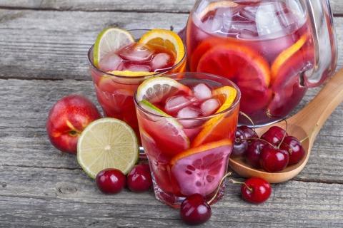 2 Gläser mit Orangenschalen, Limettenschalen, Kirschen und Eiswürfel