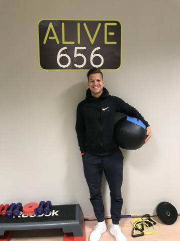 Der Inhaber des EMS Fitnessstudios Alive656, Daniel Mair, mit einem Medizinball unter dem Arm in seinem Fitnessstudio