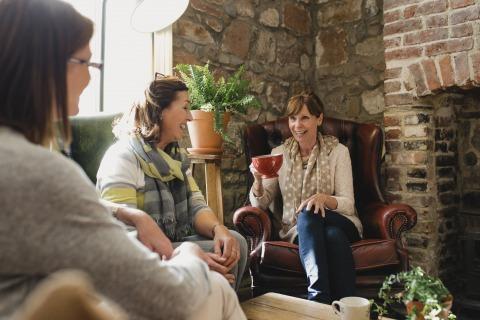 Drei ältere Damen sitzen in einem Wohnzimmer bei einer Tasse Kaffee zusammen