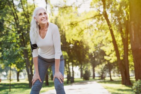 Eine sportliche ältere Dame legt eine Pause während des Lauftrainings ein