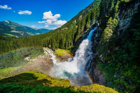 Panoramaaufnahme der mächtigen Krimmler Wasserfälle, deren Wasser einen Felsabhang hinunterstürzt