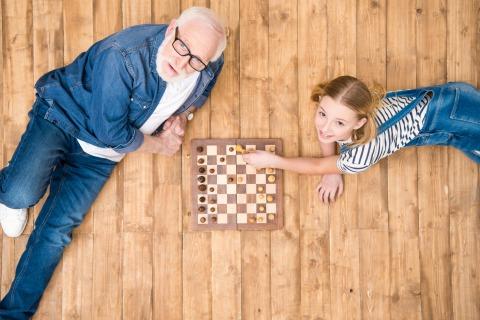 Ein älterer Herr spielt mit einem jungen Mädchen auf einem Holzboden liegend Schach
