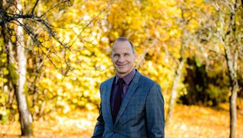 Raiffeisen-Berater Ferdinand Wallenböck steht vor einer herbstlichen Kulisse im Wald