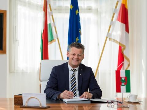Klagenfurts Bürgermeister Christian Scheider hinter seinem Schreibtisch vor einer Klagenfurt-, einer Kärnten- und einer EU-Flagge
