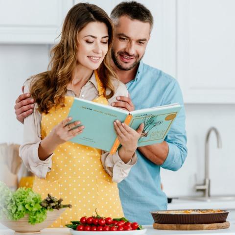 Junges Paar studiert Rezepte im Kochbuch von myLine | Credit: AENGUS Ernährungskonzepte GmbH