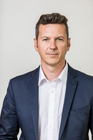 Porträt des Kärntner Landesrats Daniel Fellner, der ein offenes Sakko über einem weißen Hemd trägt