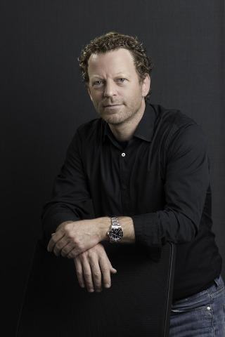 Markus Jordan, der sich mit seinen Händen auf eine Stuhllehne sützt